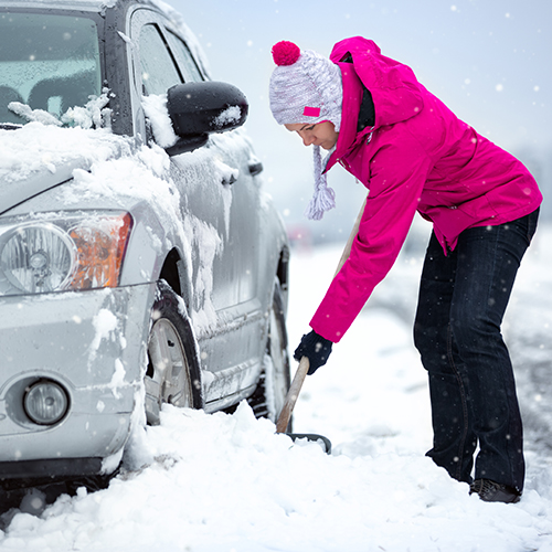Woman shoveling car in snow